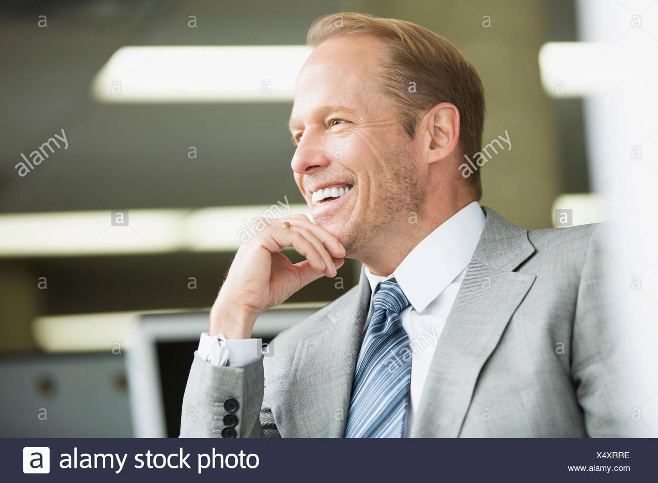 Imprenditore attraente rilassato e sorridente in ufficio Immagini Stock