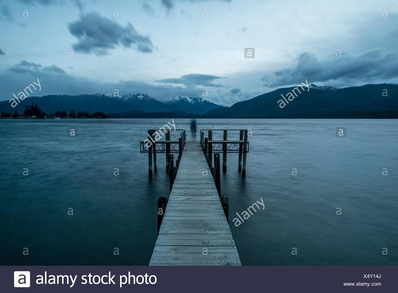 Cielo nuvoloso sulle montagne, silhouette in piedi sul dock, Lago Te Anau, Southland, Nuova Zelanda Immagini Stock