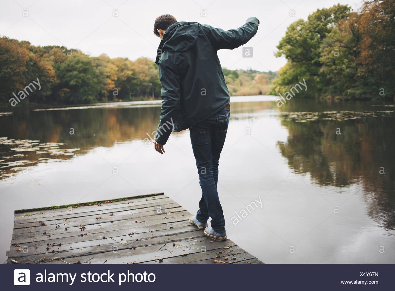 Giovane uomo a camminare lungo il bordo del fiume pier Immagini Stock