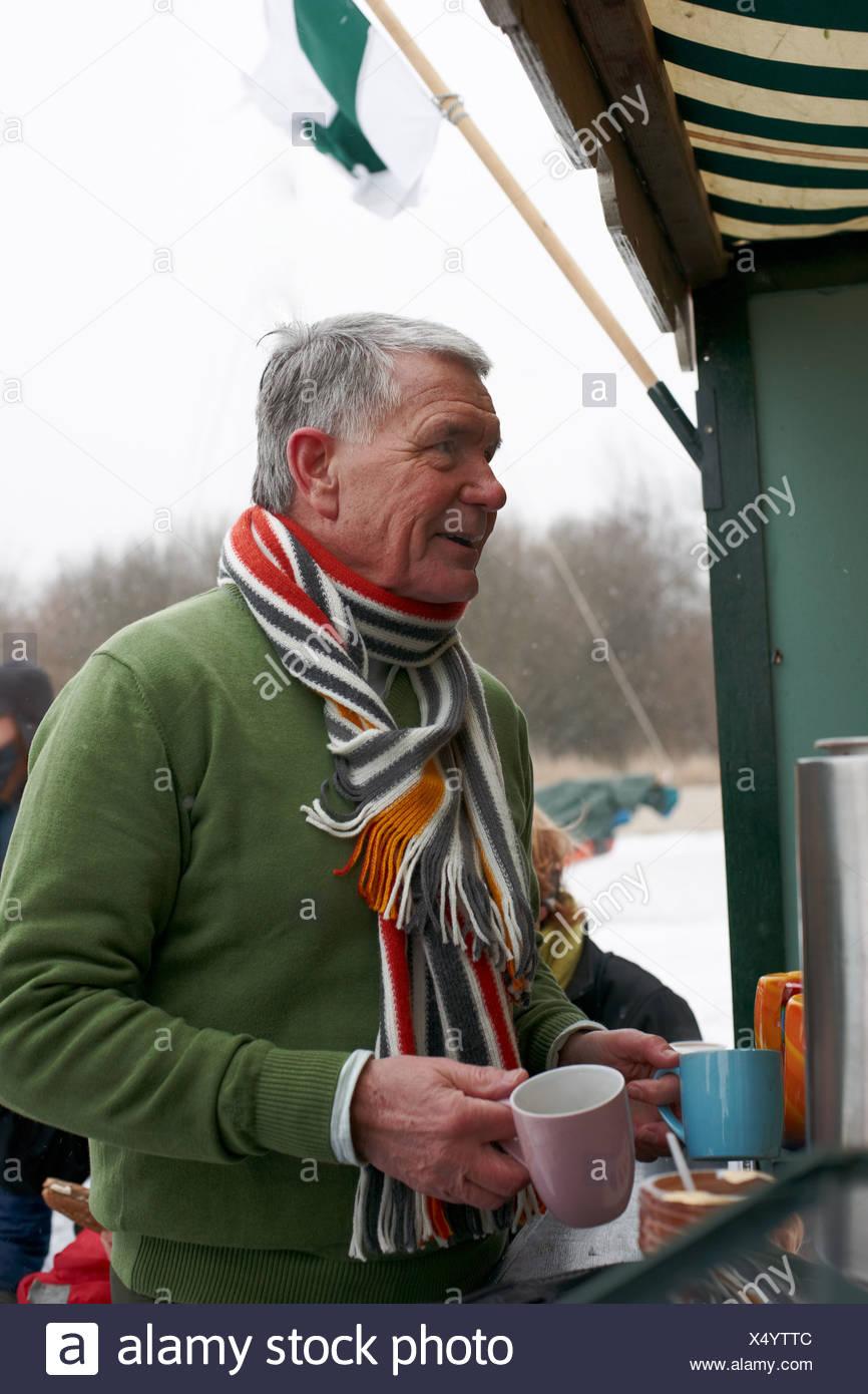 Senior uomo ottenere bevande calde a stand alimentari sul giorno di inverno Immagini Stock