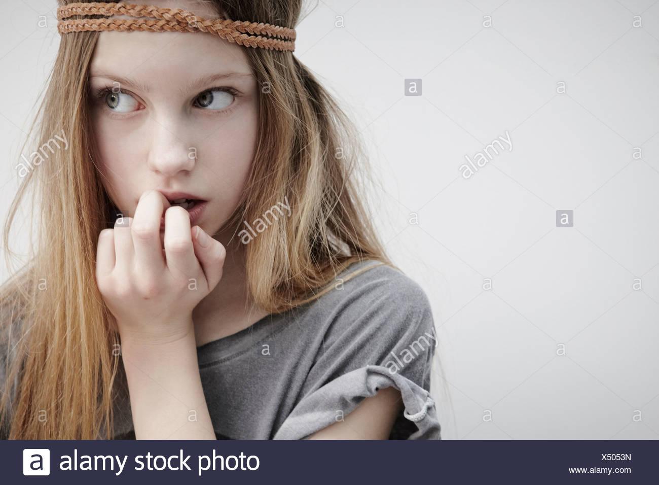 Ritratto di una ragazza che indossa la treccia in pelle attorno alla testa, tenendo giù, il dito in bocca Immagini Stock