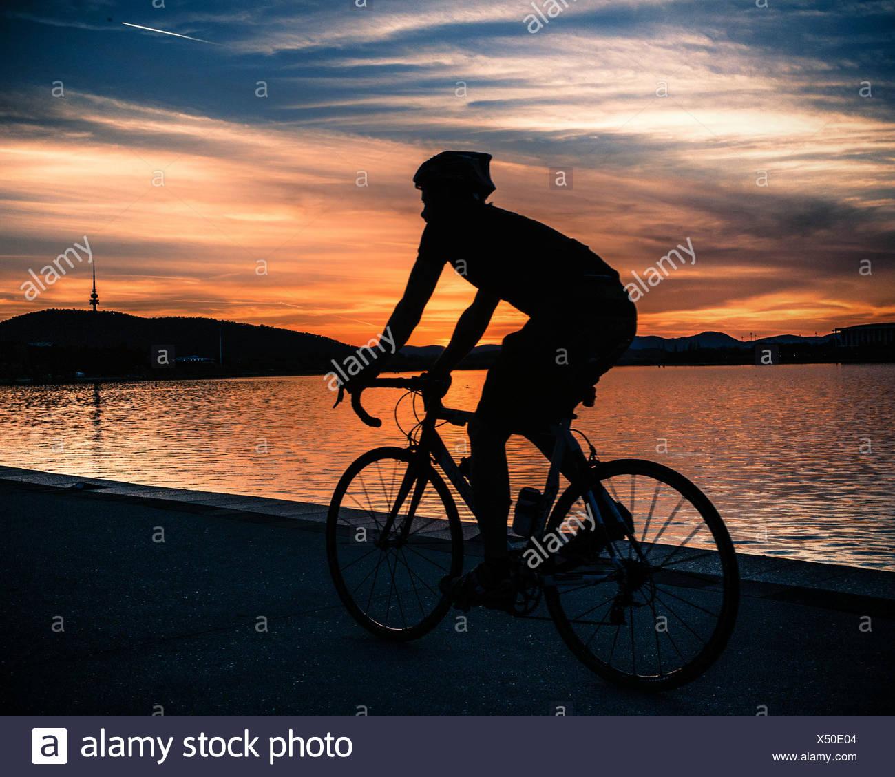 Silhouette di un ciclista al tramonto vicino al lago Burley Griffin, Canberra, Australia Immagini Stock