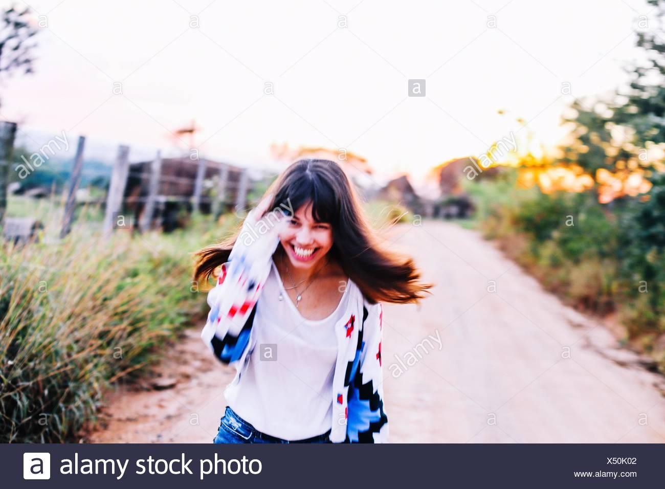Ritratto di Felice giovane donna in esecuzione su strada in mezzo le piante contro il cielo chiaro Immagini Stock