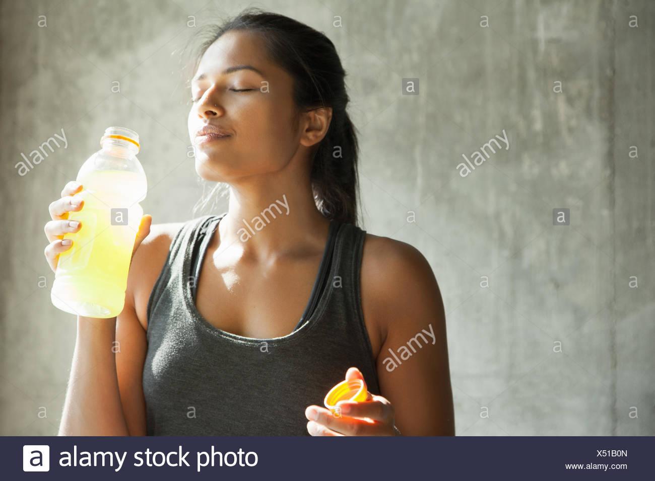 Donna con bottiglia di bevanda Immagini Stock