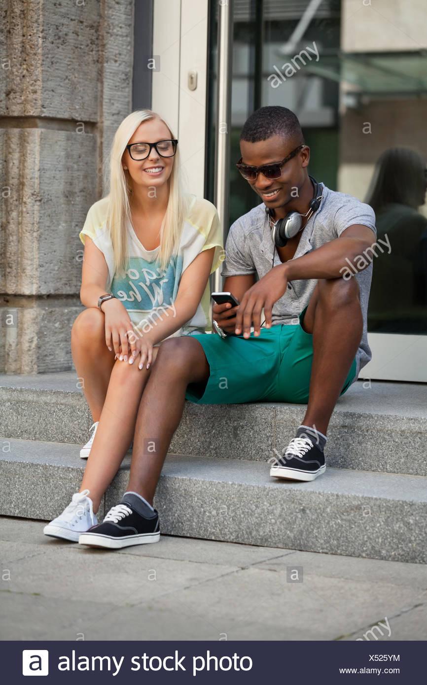Lachende junge freunde im sommer in der Stadt mit mobiltelefon Foto Stock