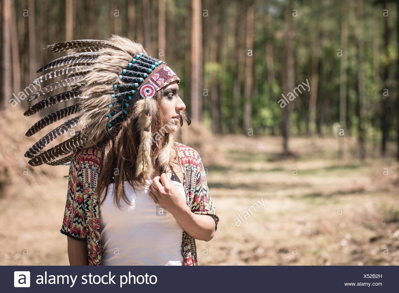 Giovane donna mascherata come un Indiano nel bosco Immagini Stock