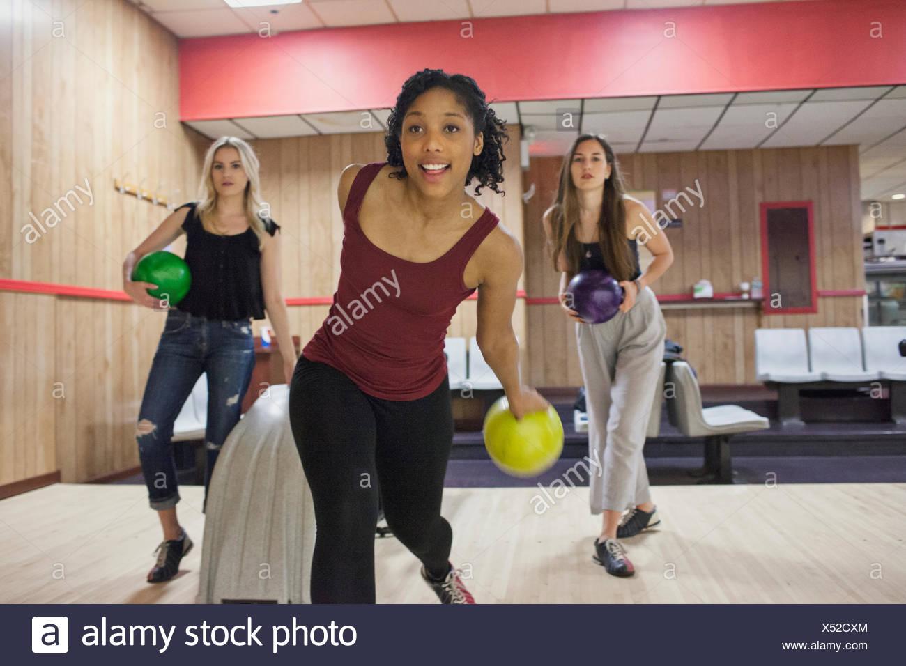Una giovane donna bowling con gli amici. Immagini Stock