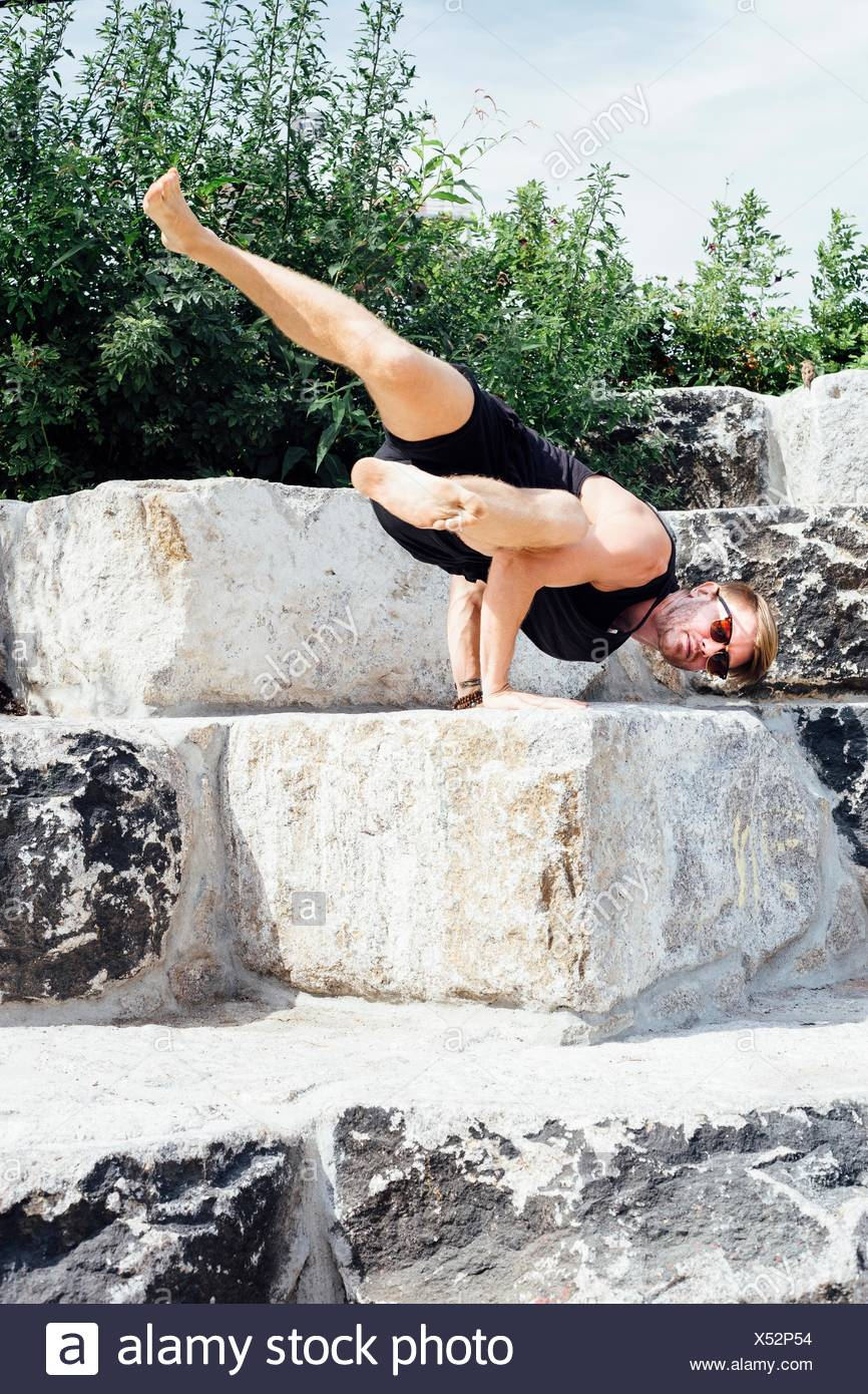 Metà uomo adulto praticando yoga avanzati handstand in fase di parcheggio Immagini Stock