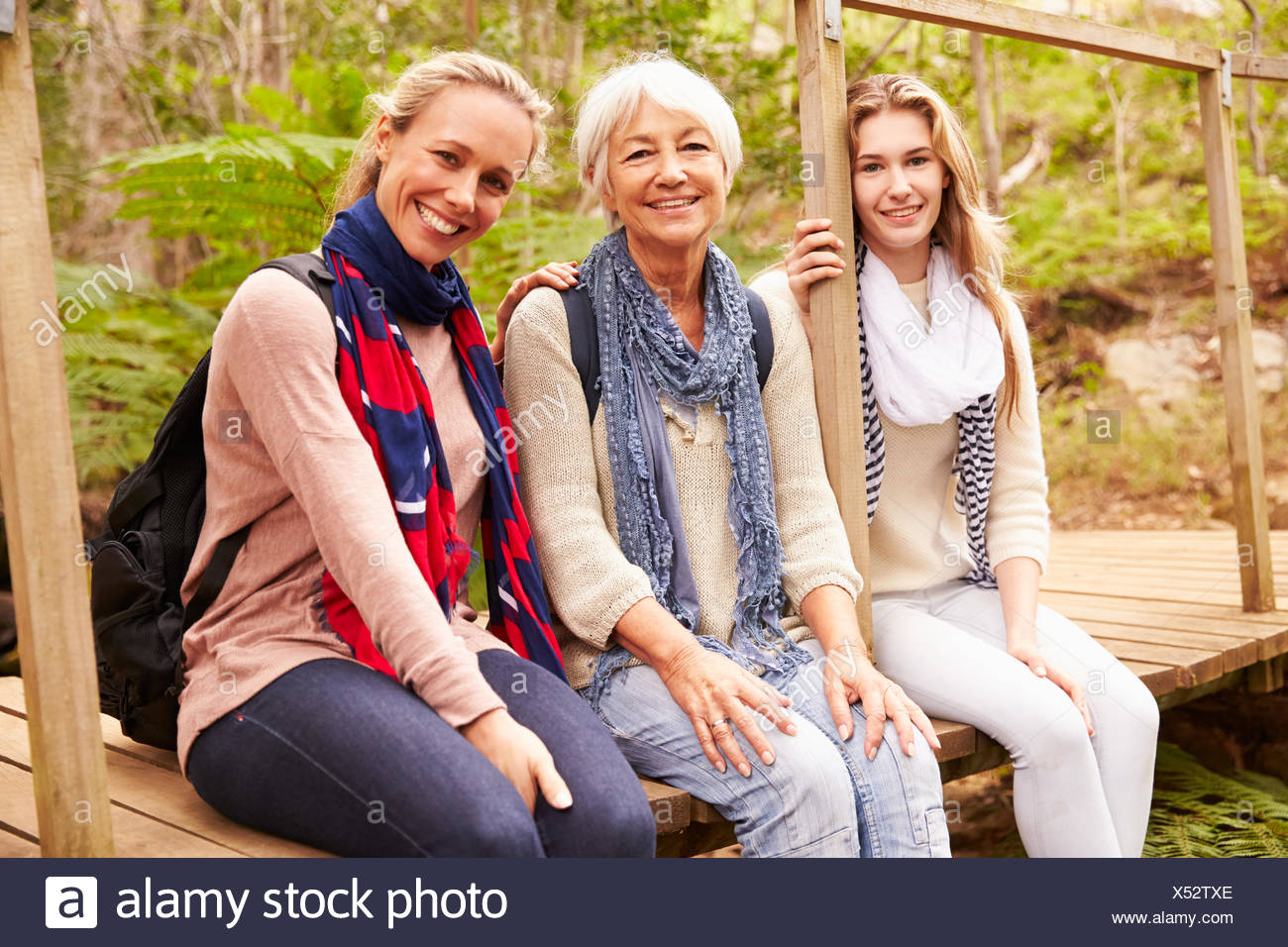 Tre generazioni di donne sedute in una foresta, ritratto Foto Stock