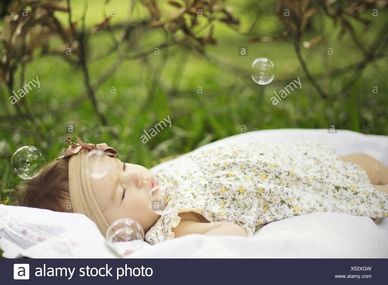 Baby girl circondato da bolle in posizione di parcheggio Immagini Stock