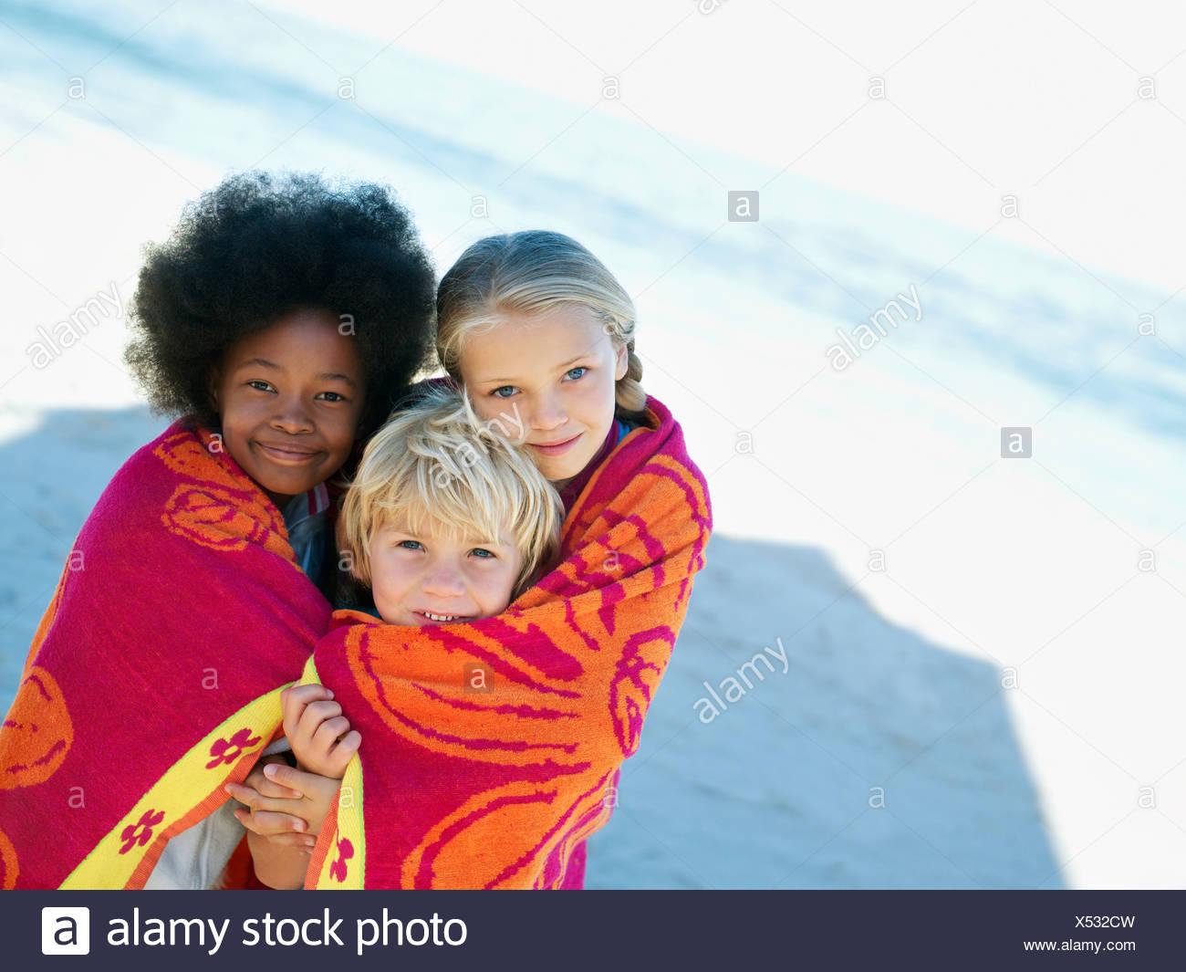Tre bambini 6 9 permanente sulla spiaggia sabbiosa avvolto in salvietta singola sorridente inclinazione verticale Immagini Stock