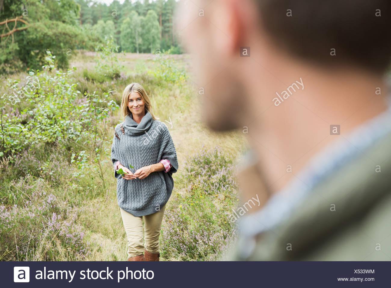 Metà donna adulta holding foglia, uomo sfocato in primo piano Immagini Stock