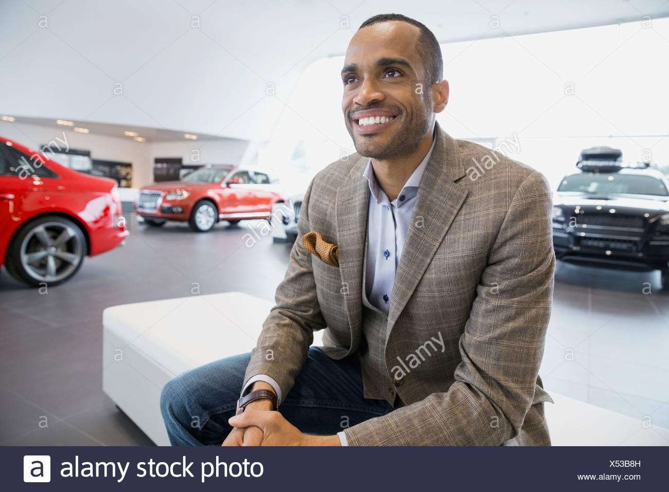 Uomo sorridente in concessionaria auto showroom Immagini Stock