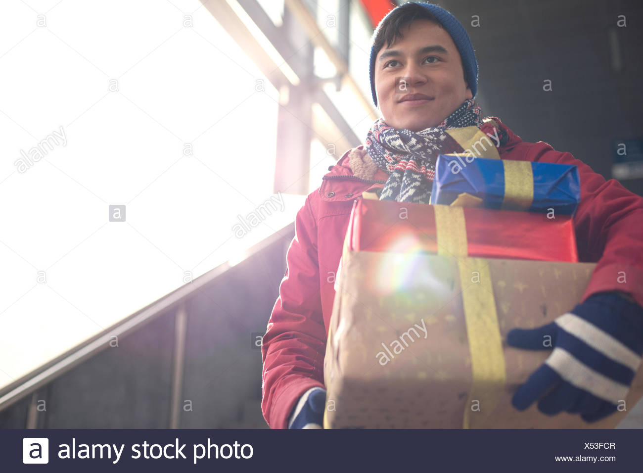 Basso angolo di visione dell uomo sorridente holding doni dalla finestra Immagini Stock