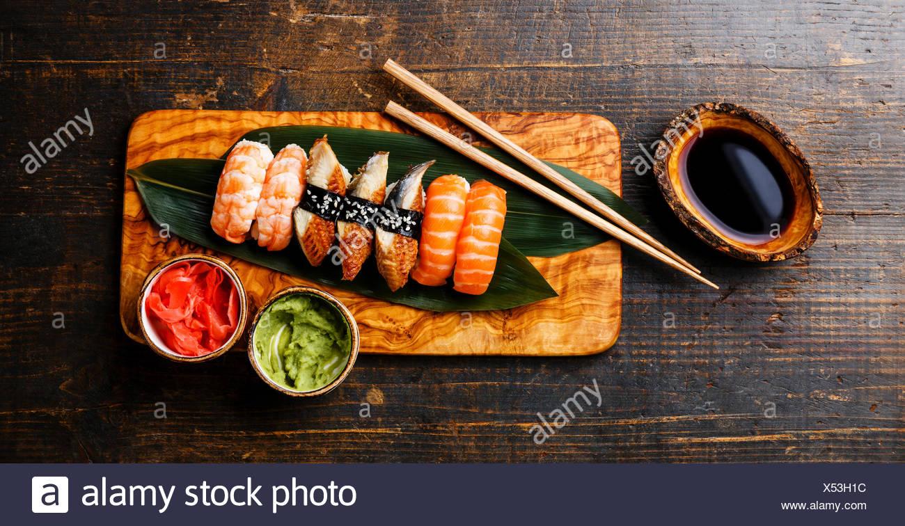 Il nigiri sushi Set su bambù foglia verde oliva su pannello di legno con salsa di soia su sfondo di legno Immagini Stock