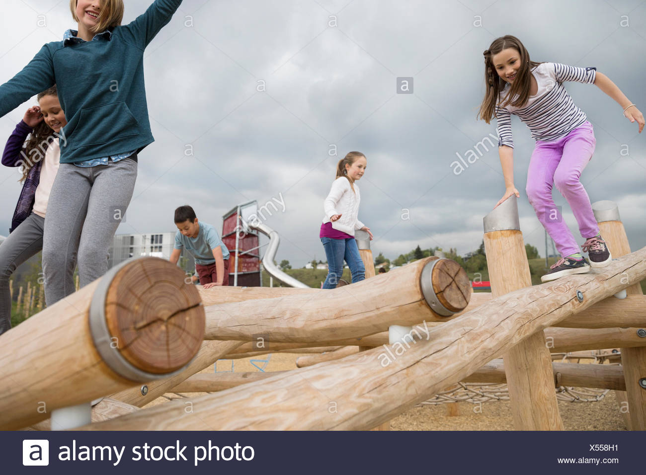 Bambini che giocano su registri presso il parco giochi Immagini Stock