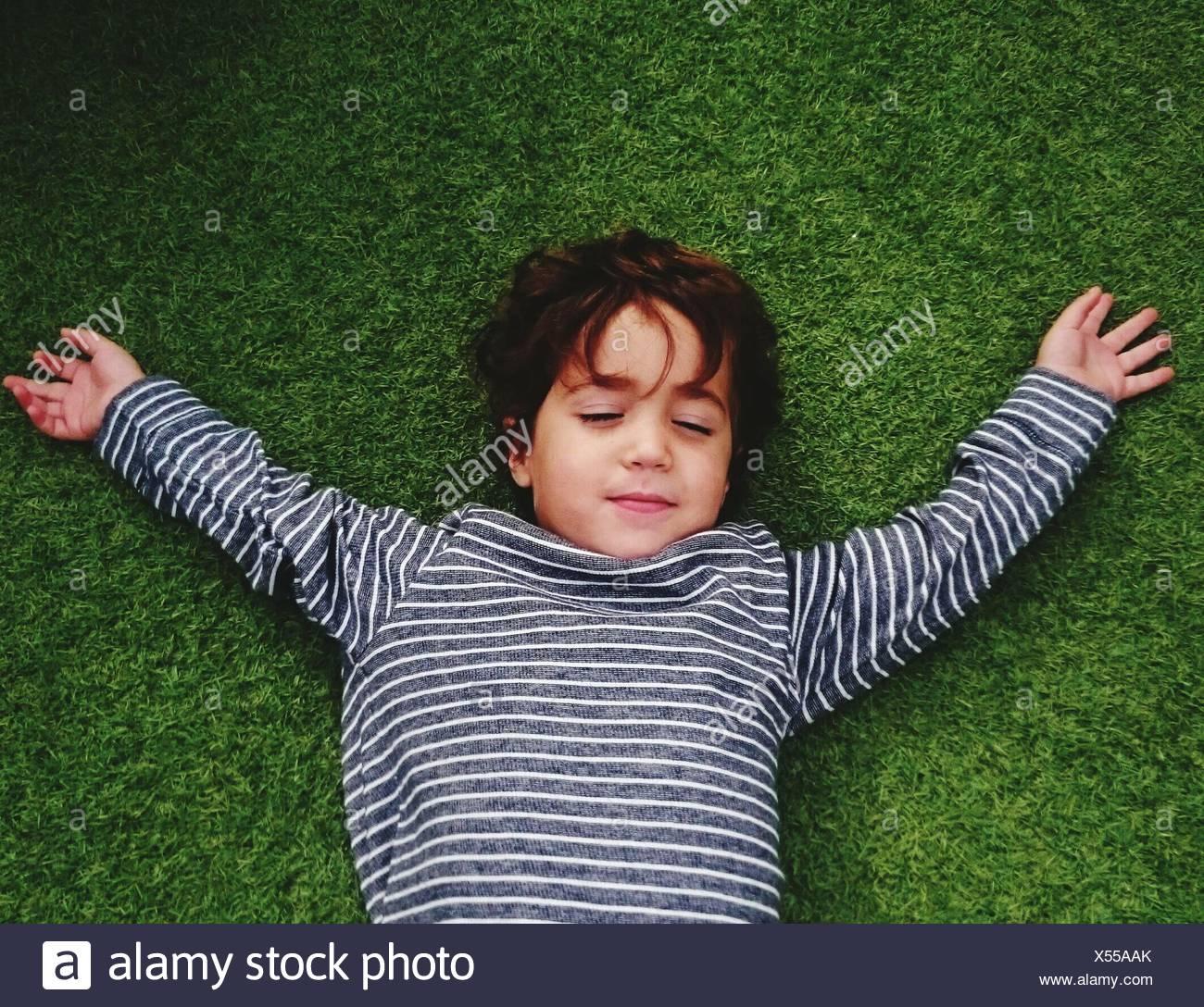 Angolo di Alta Vista del ragazzo carino in appoggio sul campo erboso Immagini Stock