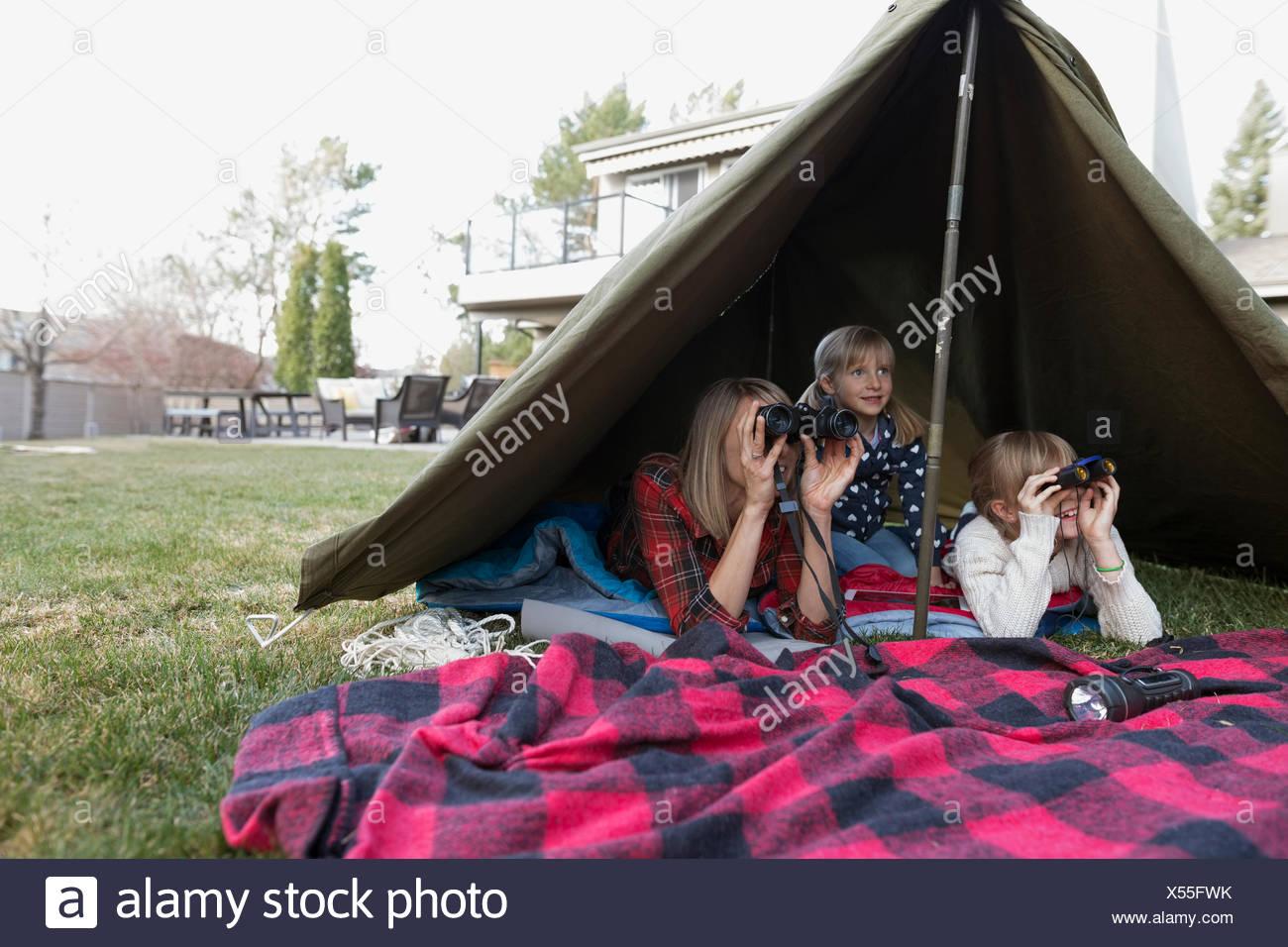 La madre e le figlie usando il binocolo in tenda nel cortile Immagini Stock