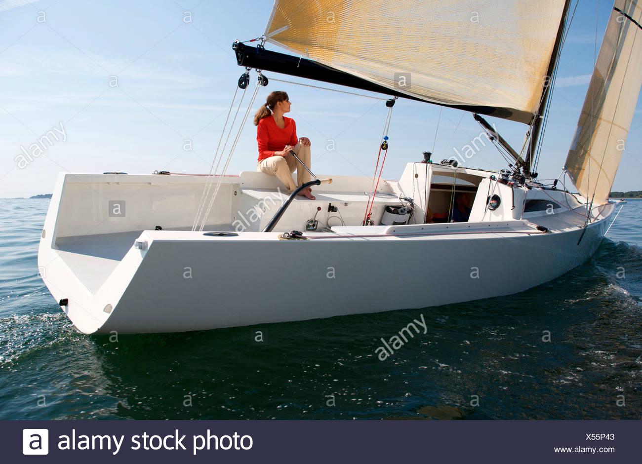 Una donna godendo una giornata di sole a bordo di un daysailer sul Casco Bay, Maine. Immagini Stock