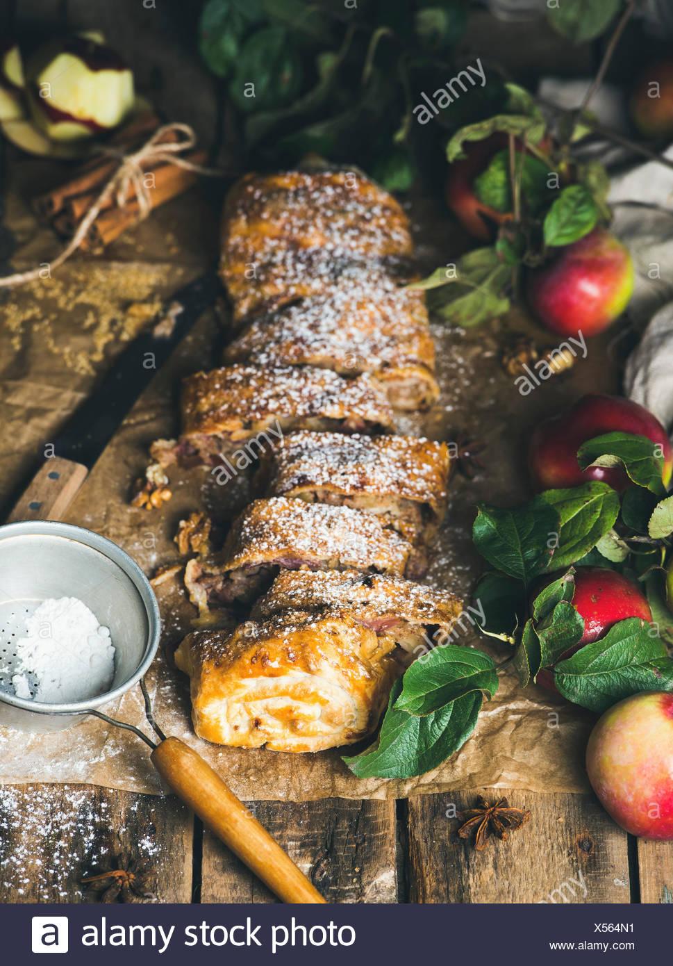 Strudel di mele torta con la cannella, lo zucchero in polvere e mele fresche sulla tavola in legno rustico sfondo, il fuoco selettivo, verticale com Immagini Stock