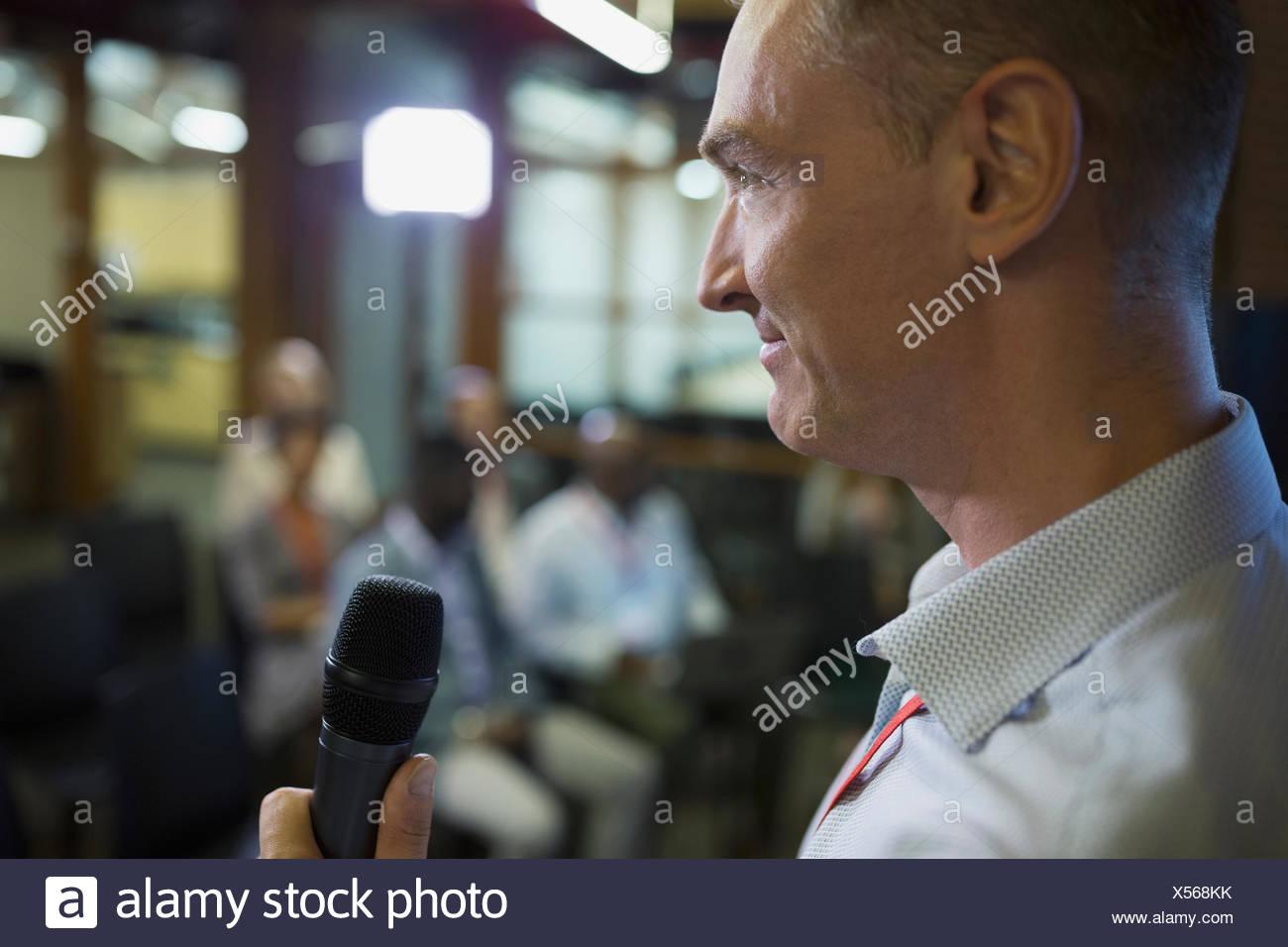 Chiudere l uomo d affari con microfono intervenendo a una conferenza Immagini Stock