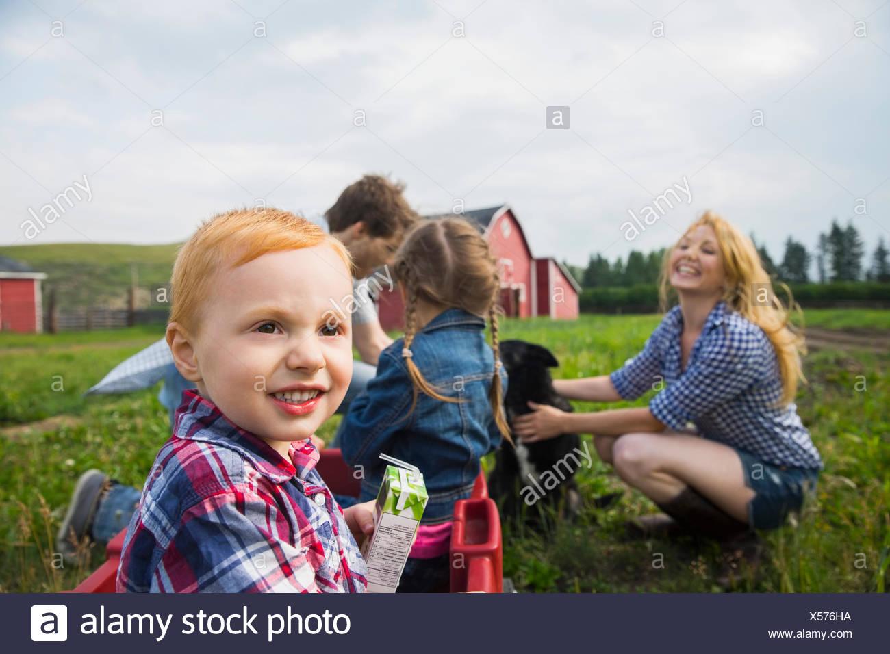 Ragazzo sorridente nel carro in campo rurale Immagini Stock