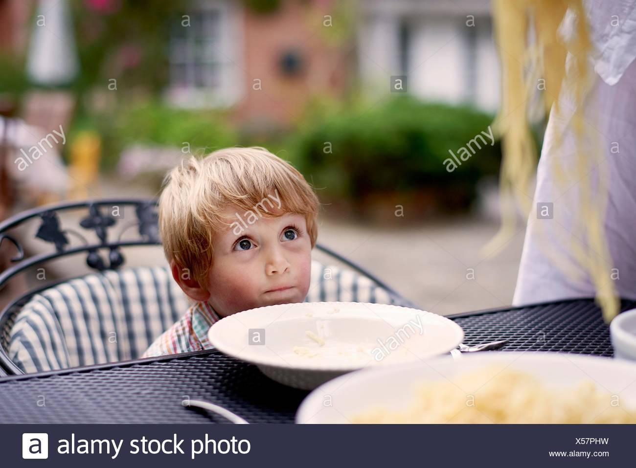 Ragazzo seduto al tavolo da giardino in attesa di spaghetti per essere servito Immagini Stock