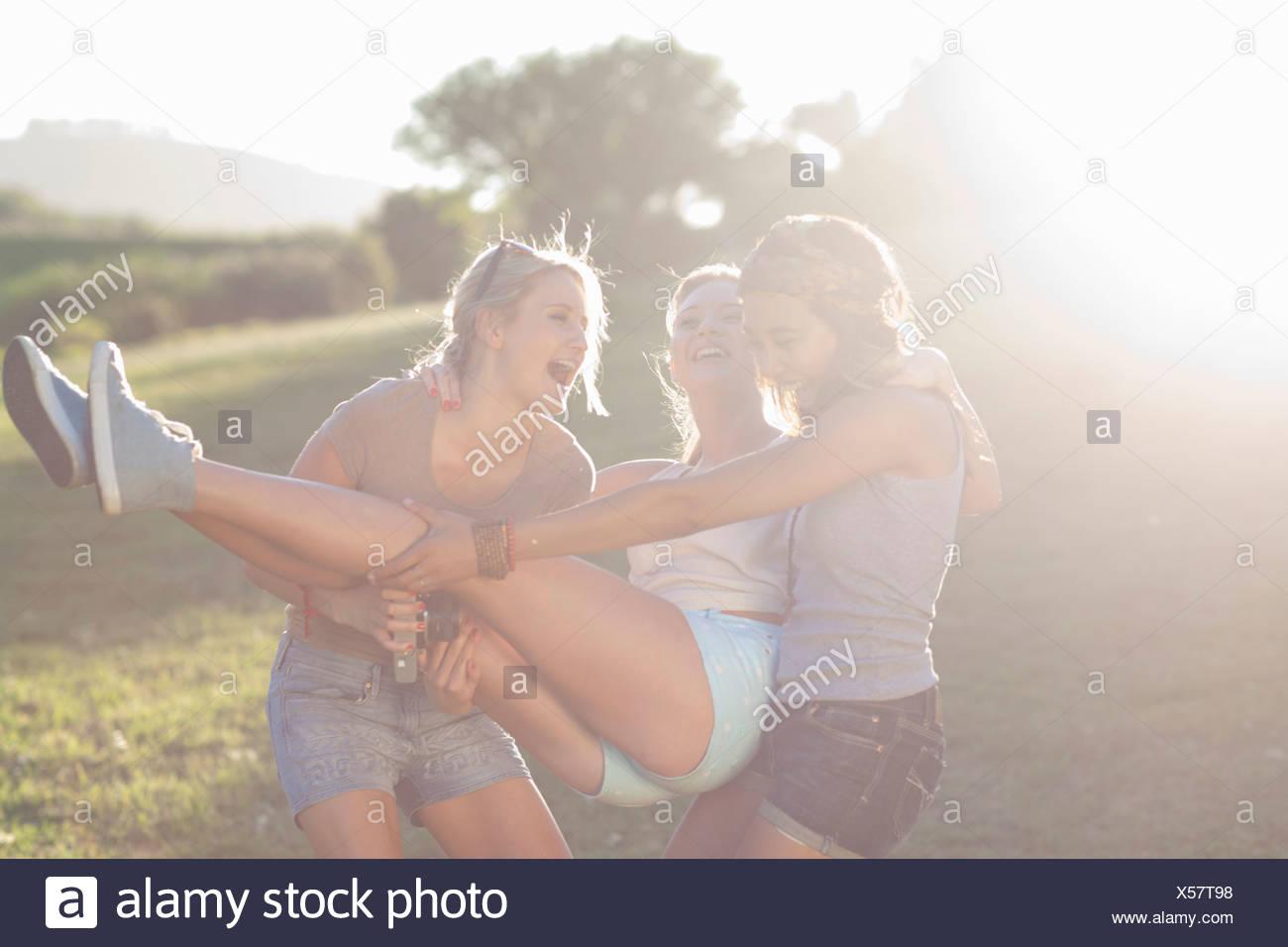 Due giovani femmine ingannare intorno cercando di portare un amico Immagini Stock