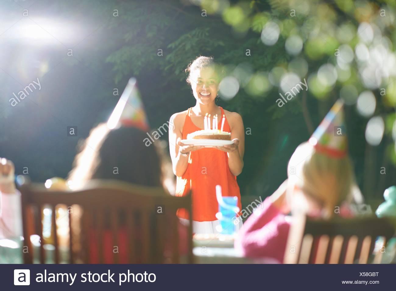 La madre che porta la torta di compleanno al tavolo in giardino festa di compleanno Immagini Stock