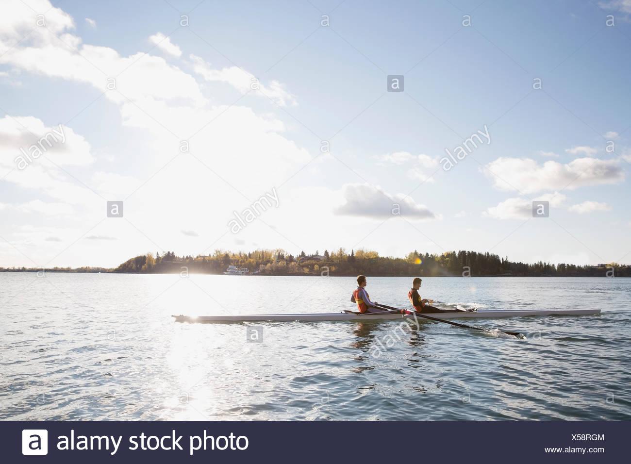 Il team di canottaggio in scull sul fiume soleggiato Immagini Stock
