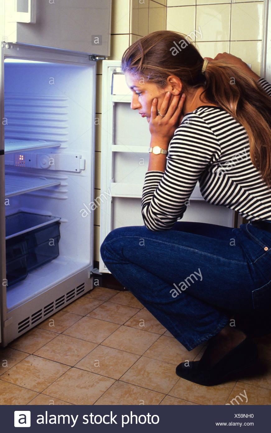 Donna che guarda in un frigo vuoto Immagini Stock