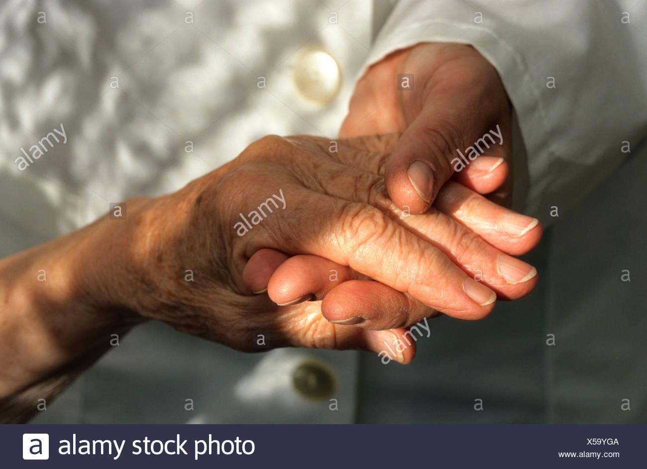 Custode mentre tiene il suo client di anziani la mano Immagini Stock