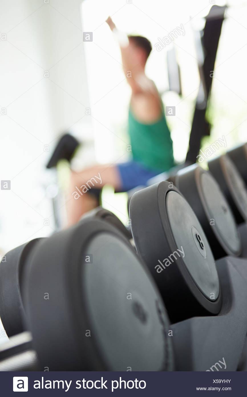 Vista astratta dell'uomo allenamento con i pesi in palestra Immagini Stock