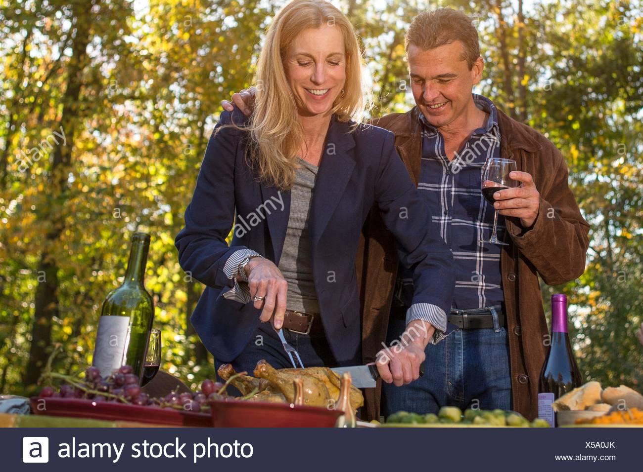 Coppia matura carving pollo arrosto al garden dinner party Immagini Stock