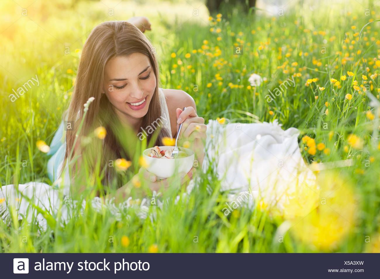 Giovane donna nel campo della renoncules mangiare frutta fresca Immagini Stock