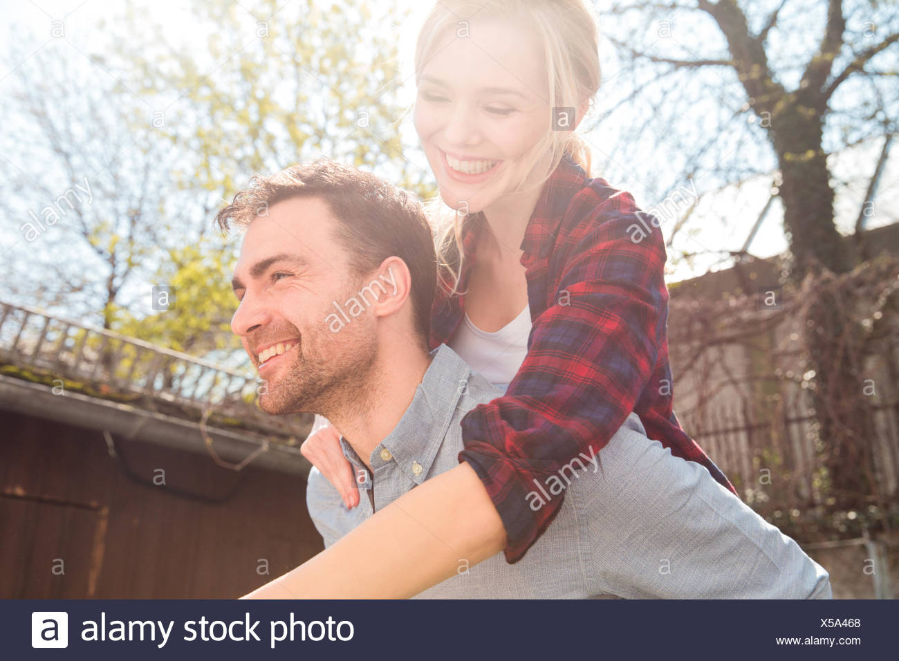Uomo Donna dando piggyback sorridente Immagini Stock