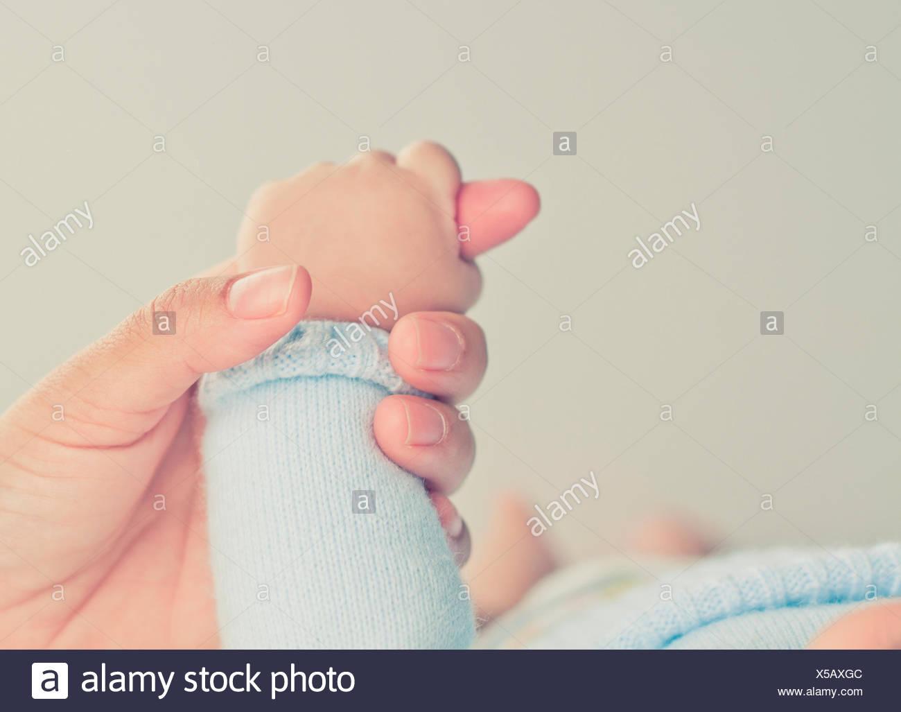 Primo piano di una mano di una madre che tiene la mano del bambino ragazzo Foto Stock