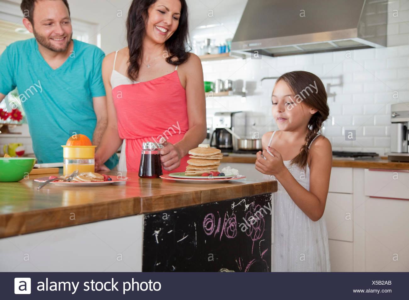 Metà dei genitori adulti tentati figlia con frittelle a colazione bar Immagini Stock