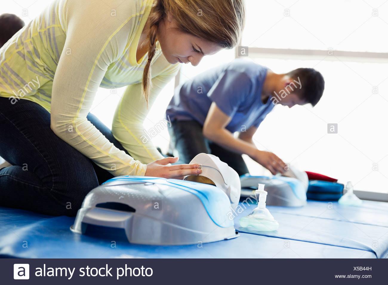 Donna praticare la RCP su fantoccio in prima classe di aiuto Immagini Stock