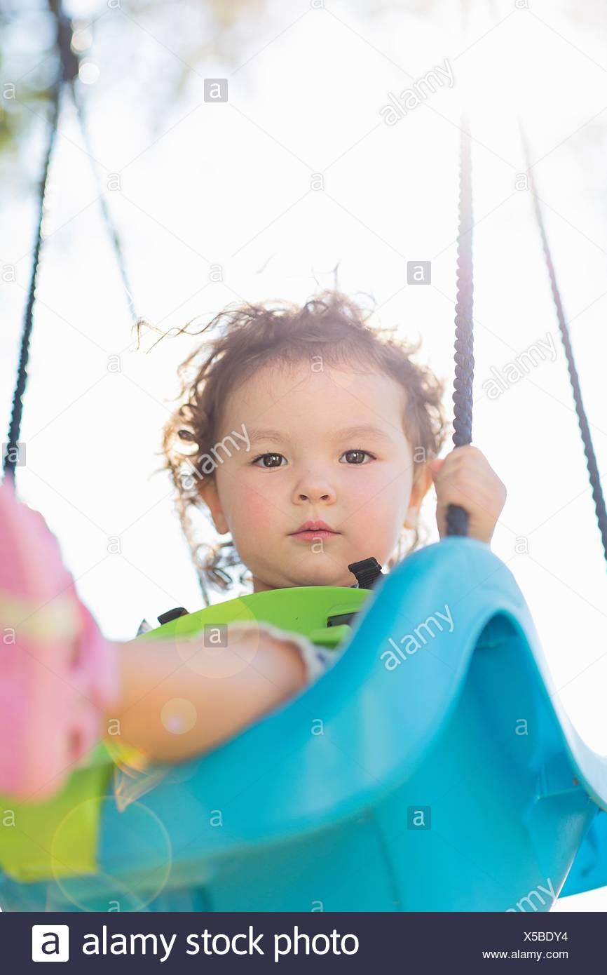 Giovane ragazza sul parco giochi altalena, basso angolo di visione Immagini Stock