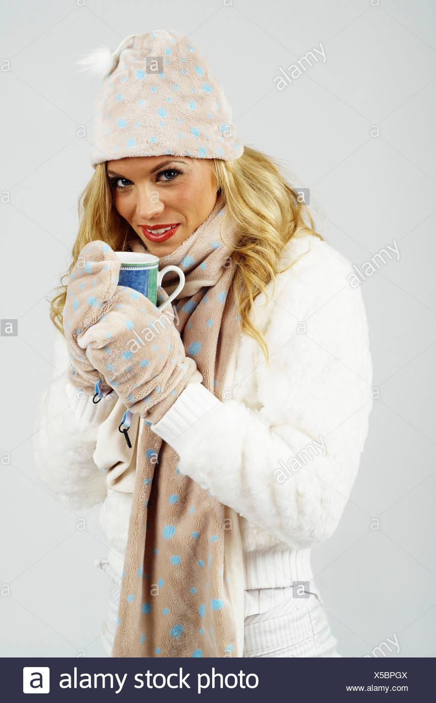 e9e55dfa2692 Giovane donna indossa abbigliamento invernale, bevendo una calda tazza di tè