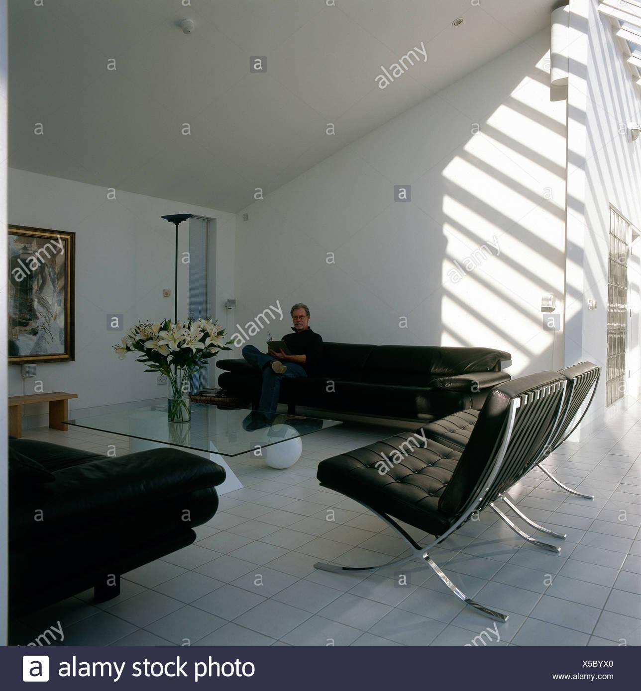 Ritratto di uomo seduto sul divano nel soggiorno moderno con pelle ...