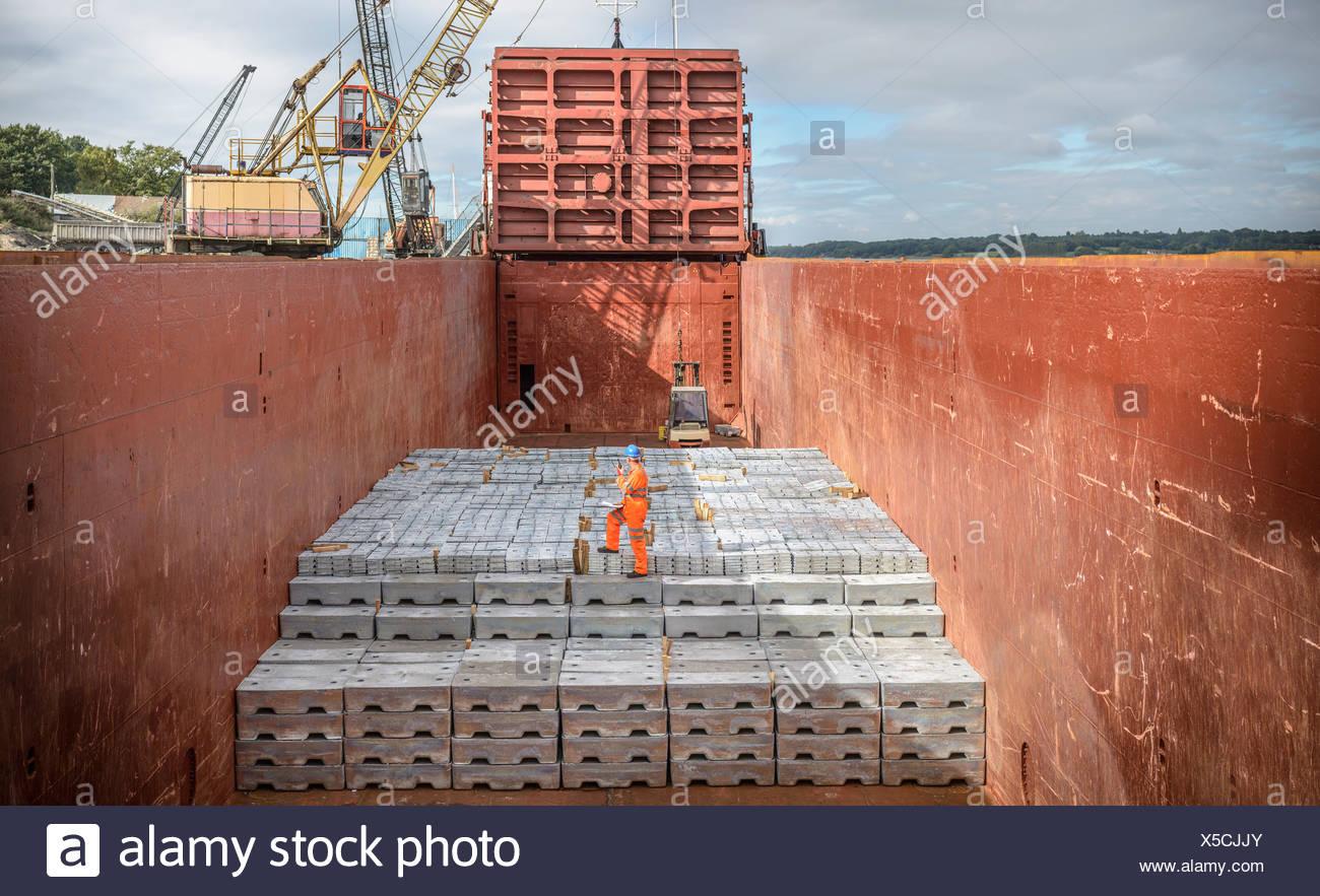 Lavoratore permanente sulla lingotti di metallo delle stive delle navi Immagini Stock