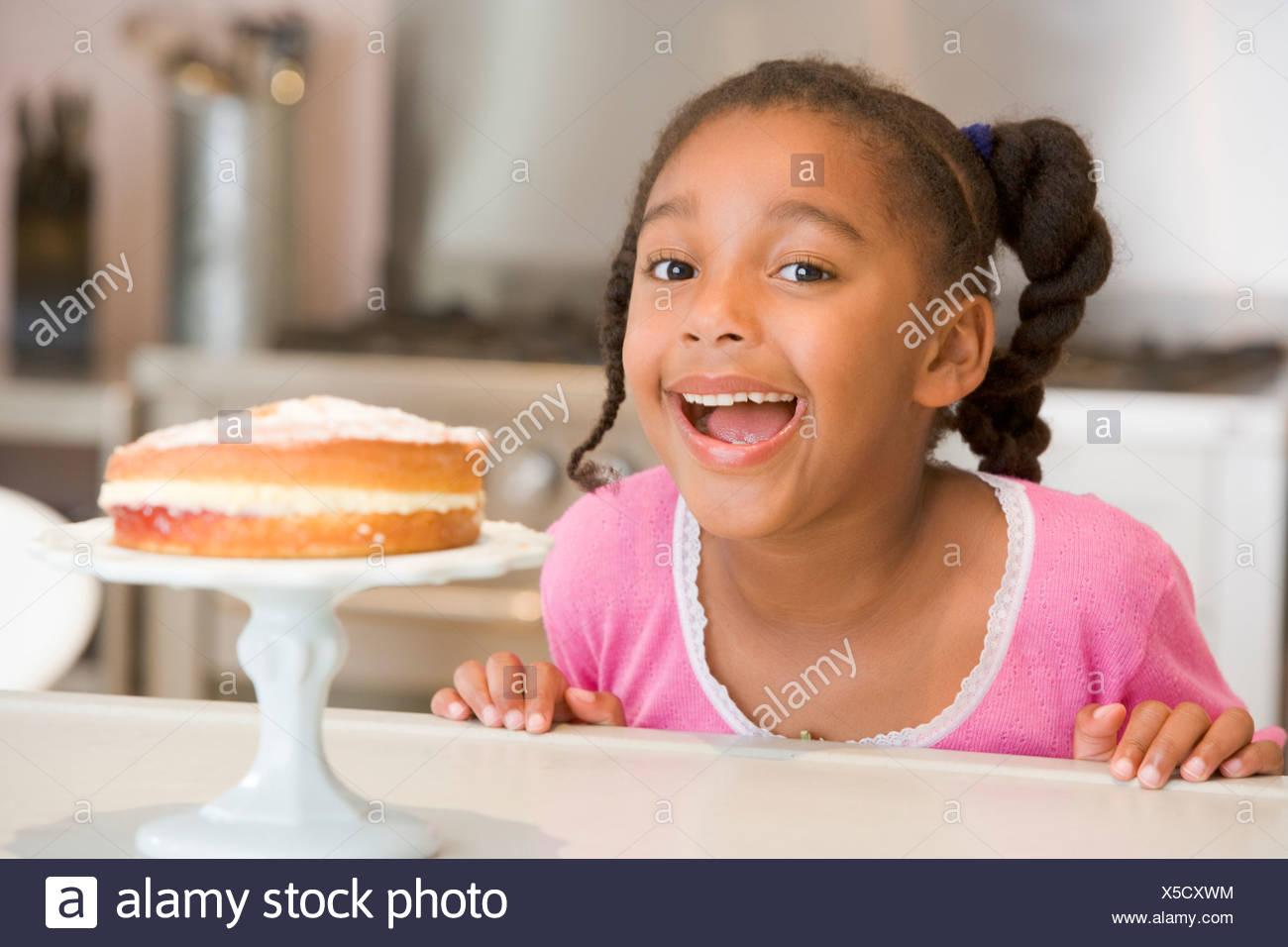 Giovane ragazza in cucina guardando la torta sul contatore sorridente Immagini Stock