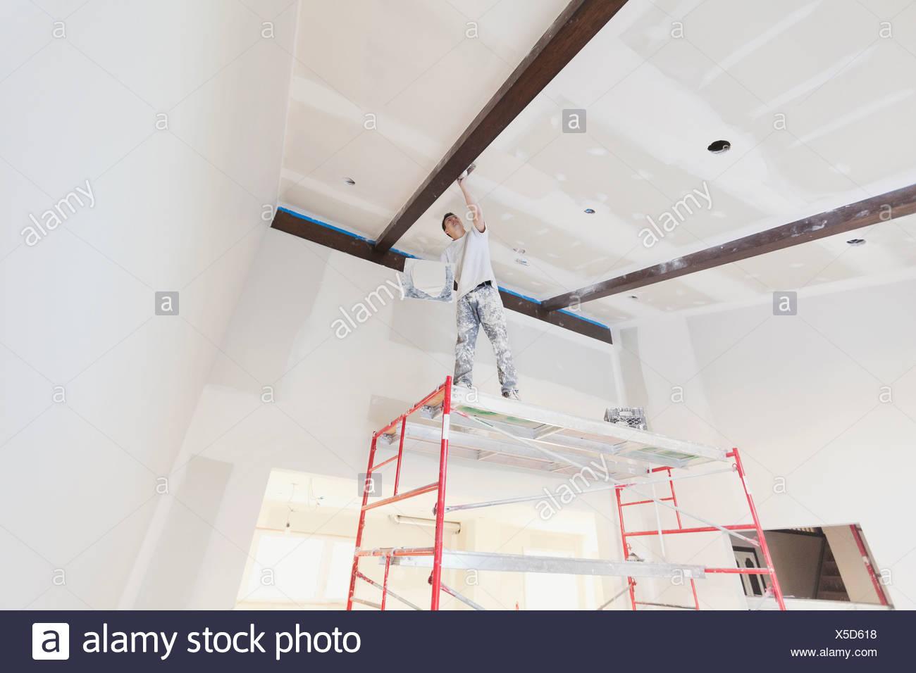 Basso angolo di vista tradesman intonacatura muro a secco in casa Immagini Stock