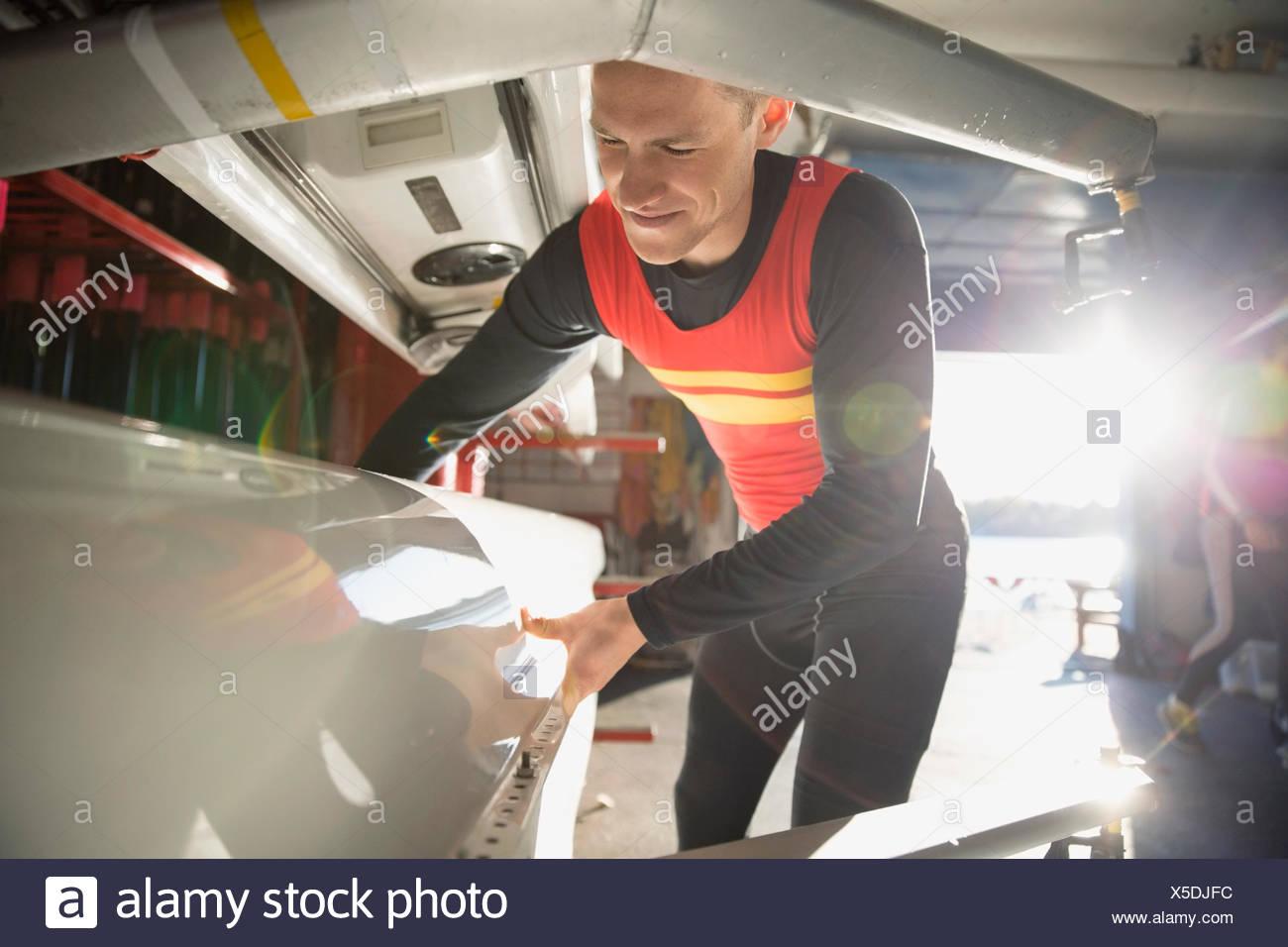 Vogatore scull sollevamento dal rack in boathouse Immagini Stock