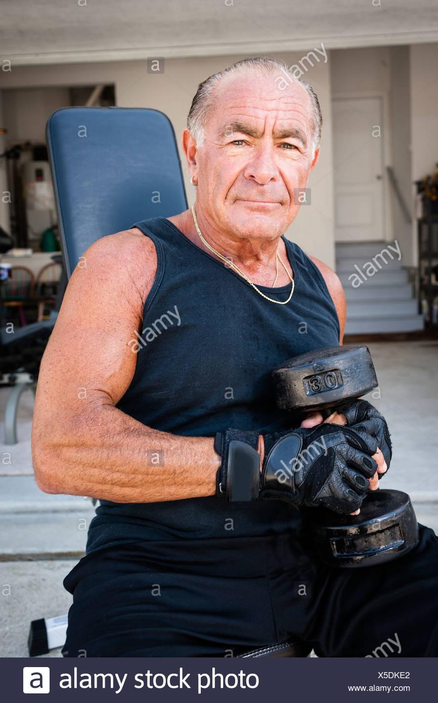 Ritratto di muscolare uomo senior holding dumb campane Immagini Stock