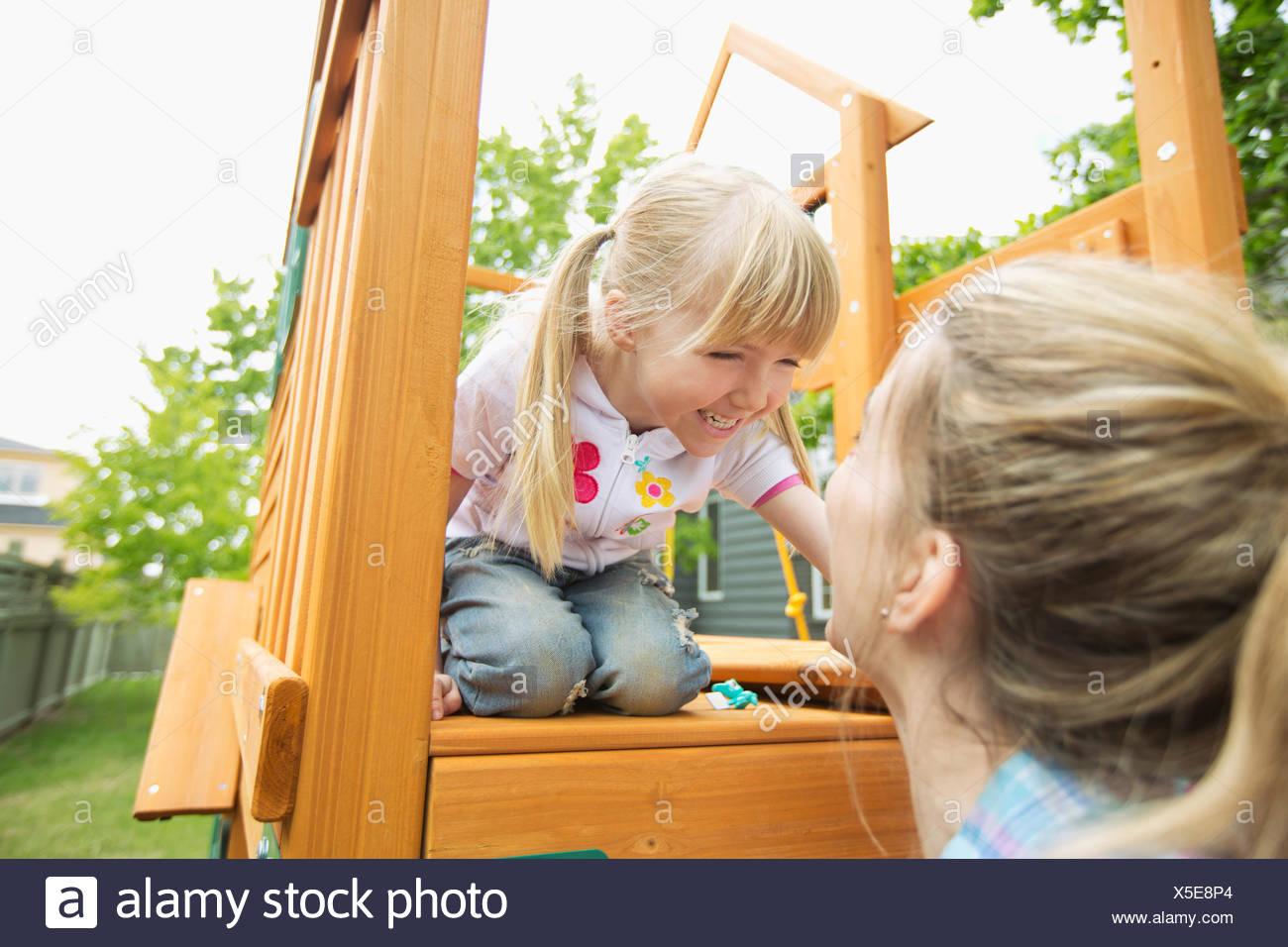 Mamma e figlia in cortile con struttura di gioco Immagini Stock