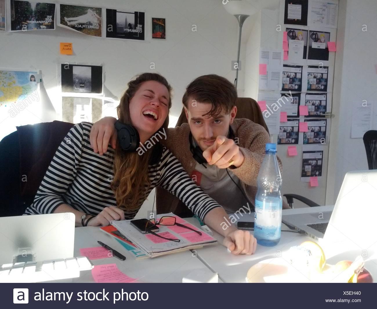 Allegro giovane donna con uomo rivolto a voi in ufficio creativo Immagini Stock