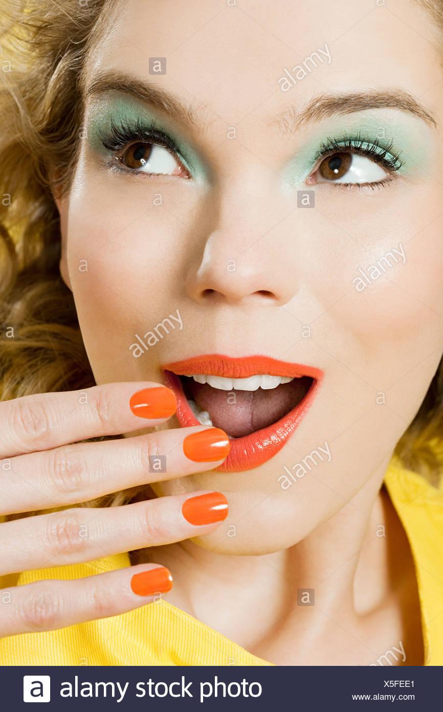 Sorpreso di giovane donna bionda contro sfondo giallo Immagini Stock